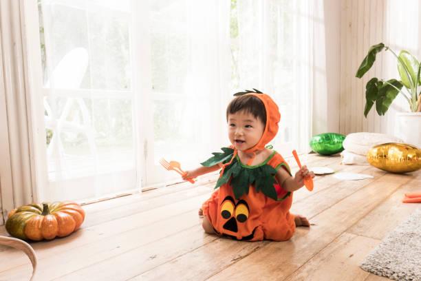 Petit garçon qui porte un costume de citrouille et joue sur le sol du salon