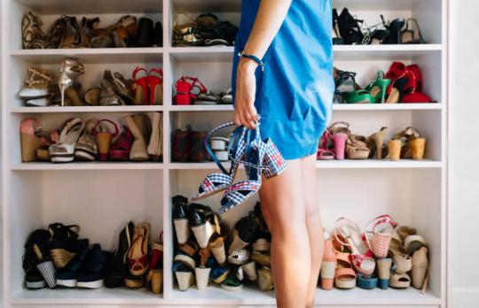 femme devant un placard rempli de chaussures tenant une paire de sandales à talons à la main
