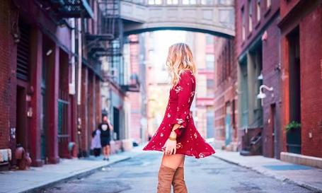 femme blonde portant une robe rouge avec des cuissarde camel dans une rue