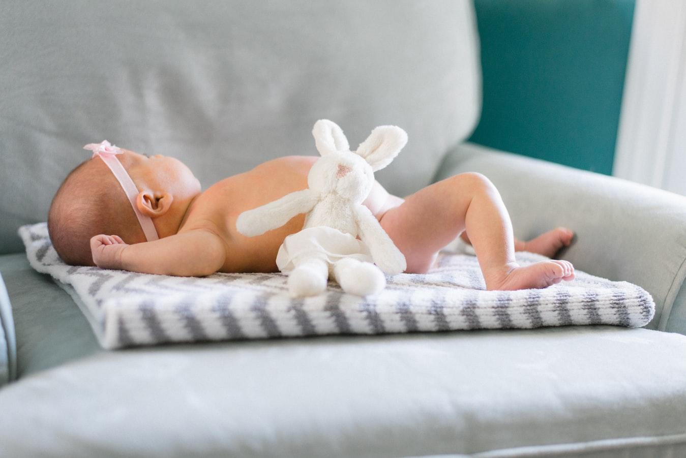 bébé entouré de ses cadeaux de naissance comme un doudou